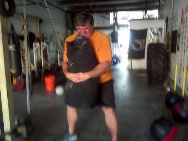Sandbag bear-hug squats with 160lb