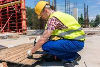 89273634-side-view-of-a-young-worker-wearing-safety-vest-and-yellow-hard-hat-while-hammering-a-nail-into-wood